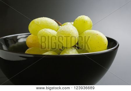 Fresh ripe bunch of grapes placed in black ceramic bowl close up on gradient background