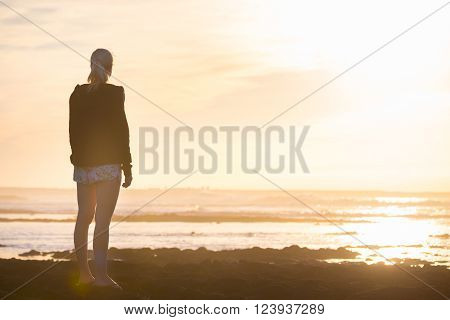 Silhouette of casualy dressed sporty woman watching sunset at the beach.