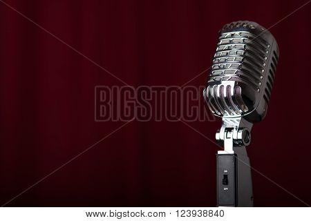 A vintage microphone on a stage in front of a red curtain