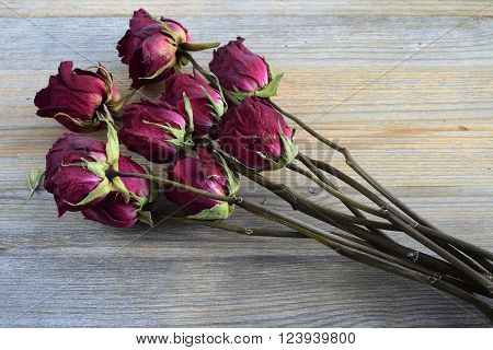 bouquet of withered roses on a wooden background