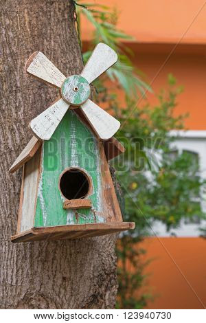 Hand made wooden bird house with white windmill with real bird nest inside, hanging on mango tree