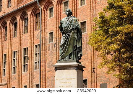 TORUN, POLAND - JULY 7, 2009: Monument of Nicolaus Copernicus holding an astrolabe in front of the old town hall on a granite pedestal bearing a Latin inscription in gold letters