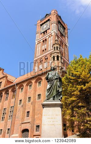 TORUN POLAND - JULY 7 2009: Monument of Nicolaus Copernicus holding an astrolabe in front of the old town hall and tower on a granite pedestal bearing a Latin inscription in gold letters