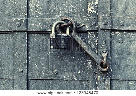 Steel black padlock hanging with old door heck at the iron forged old door. Selective focus at the padlock and door heck. Textured architectural background