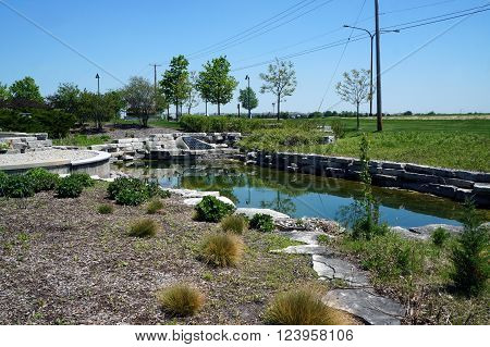 PLAINFIELD, ILLINOIS / UNITED STATES - MAY 22, 2015: A retention basin holds storm water runoff outside the Edward Outpatient Center and Emergency Department in Plainfield, Illinois.