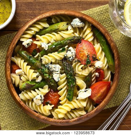 Baked green asparagus, cherry tomato, blue cheese and rotini pasta salad served in wooden bowl, photographed overhead on dark wood with natural light
