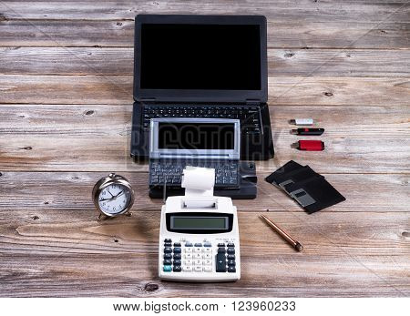 Evolution of technology starting with vintage adding machine and ending with modern laptop computer.