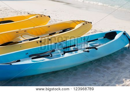 kayaking, leisure, water sport and summer vacations concept - canoes or kayaks on sandy beach