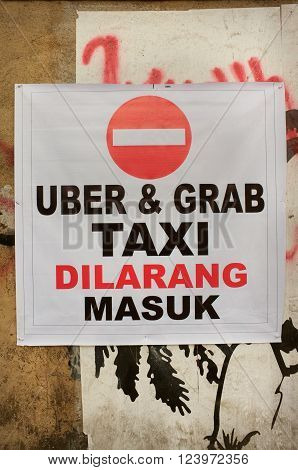 BALI INDONESIA - February 17 2016: An unofficial protest sign on a wall in Indonesian objects to Uber and Grab taxi drivers reads 'Uber and Grab Taxis No Entry' in the tourist village of Ubud Bali Indonesia.