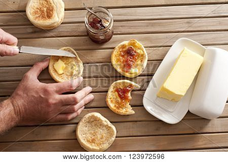 Man buttering a freshly toasted crumpet for breakfast overhead view of his hands the crumpets jam and a pat of farm butter on a slatted wooden table