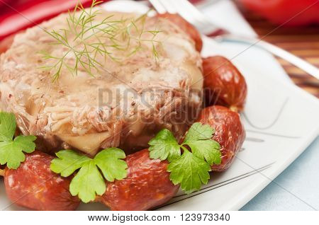 Traditional Russian food. Aspic pork jelly and smoked sausages.