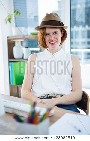 smiling hipster business woman sitting at her desk, wearing a trilby