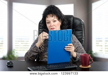 Mature woman sits in black leather office chair and sympathetically looks at the camera. She is certified psychiatrist. Black haired woman holds blue clipboard pad holder with left hand. There are keyboard mouse and maroon mug on the black desk