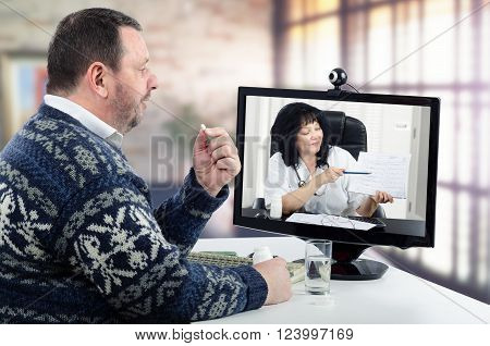 Bearded man in Scandinavian sweater takes pill during virtual doctor session. Middle-aged man suffers from high blood pressure. In the monitor physician in white hospital uniform shows his blood pressure graph. The man receives a telemedicine care