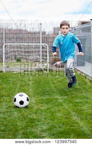 7 Years Boy Kicking Ball In The Garden.