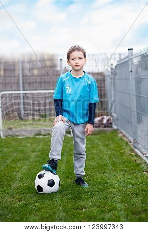 7 years boy - footballer kicking ball in the garden. Child playing football in garden. Wears a blue t-shirt, black and blue shoes and grey sweatpants