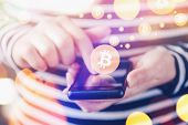 Woman paying with Bitcoins over smartphone close up of female hands using mobile phone device to complete online shopping transaction nice bokeh close up with selective focus and shallow depth of field. poster