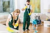 Young professional cleaners cleaning accurate spacious apartment. Man mopping the floor and girl polishing the table poster