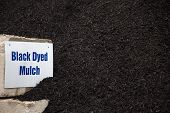 bulk pile of black dyed mulch used for landscaping projects poster