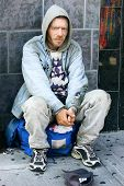 an homeless person is sitting on his backpack. poster
