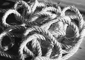 Vintage toned image of hank large ship's rope on the background of a brown wooden table. Hank of twine. poster