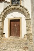 The Romanesque lateral doorway of the Church of Saint Mary with a perfect double arch and original imposts in Torres Vedras Portugal poster