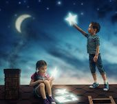 Fairy tale! The children hung the stars in the sky. Boy and girl on the roof cut out stars. poster