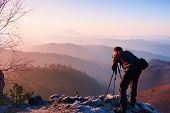 Professional photographer takes photos with camera on tripod on rocky peak. Dreamy fogy landscape, spring orange pink misty sunrise in a beautiful valley below poster