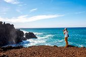Male tourist photographing on the volcanic coast Los Hervideros on Lanzarote island in Spain poster