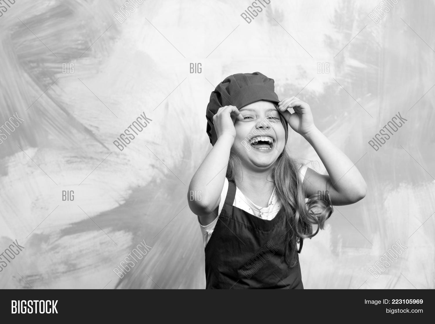 46cdaa36c71 small baby girl or cute child with happy face in red chef hat and cook apron  on colorful abstract background