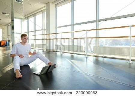 Guy dancing with laptop lessons at gym studio. Young man wears white suit. Concept of Internet tutorial for beginners.