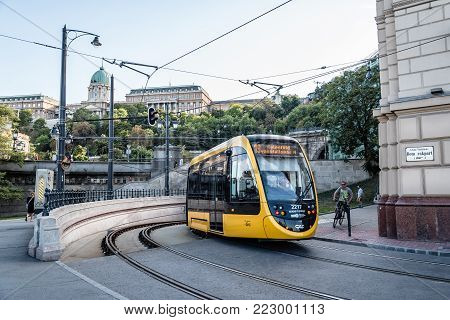 Budapest, Hungary - August 14, 2017: Scenic view of yellow tramway against Buda castle.