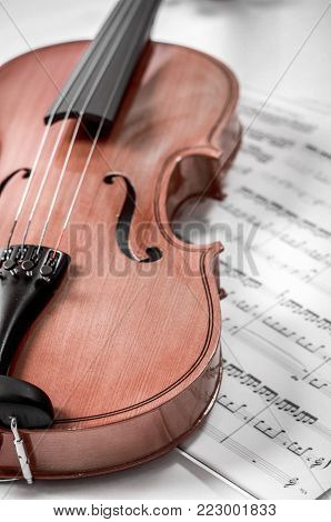 Old violin lying on the sheet of music, music concept.