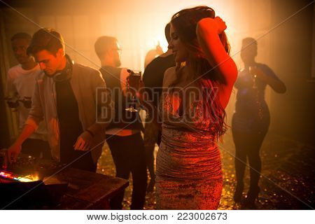 Portrait of beautiful young girl dancing elegantly in middle of dim dance floor holding champagne glass and wearing fashionable velvet party dress