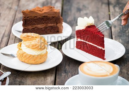 Close-up of woman's hand holding fork to eating Red velvet cake, chocolate cake, Shu cream (Japanese cream puff) and hot coffee on wooden table in outdoor garden. Concept sweets enjoy eating.