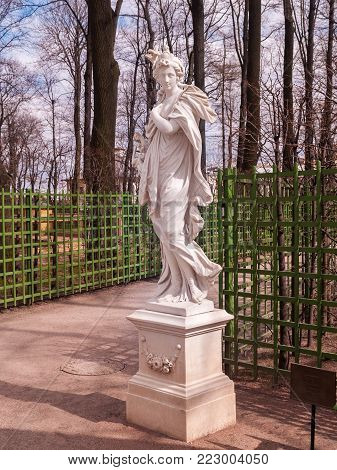 The statue of Ceres in the park Summer garden near the green grid to support plants in April in early spring before the start of the summer park season in St. Petersburg