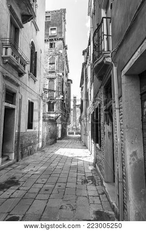Architecture of medieval Venice. Houses peeling off from dampness. Black and white picture