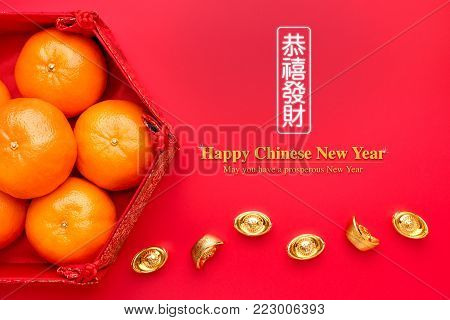 Group of orange tangerine in Chinese pattern tray with gold ingots on red table.Chinese Language on ingot mean wealthy and lable mean May you have a prosperous New Year