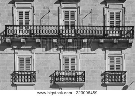 Building with traditional maltese windows in historical part of Valletta. Black and white picture