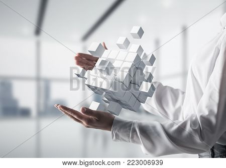 Cropped image of business woman hands holding multiple white cubes in hands with office view background. Mixed media.