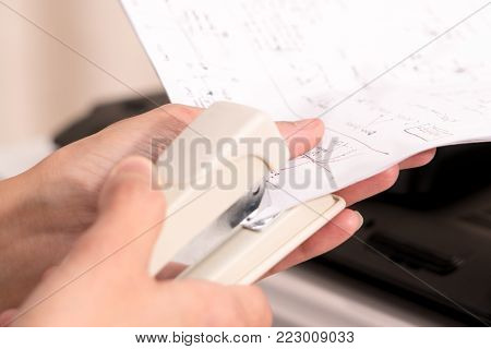focus on the women hand stapling the hand writing paper, working and office concept