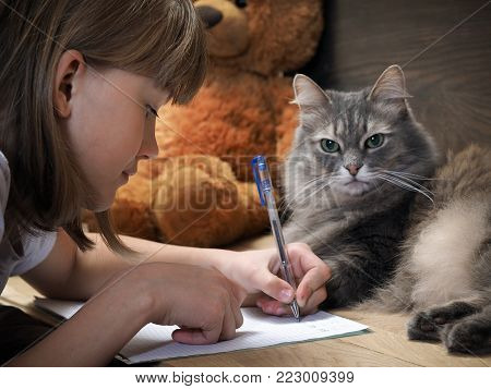 Girl doing homework, writing in a exercise book . On table is cat