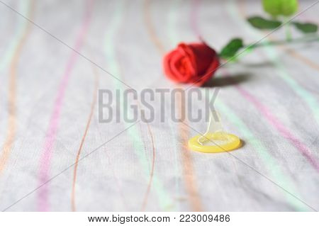 Used condom and a blurry red rose on pink bed linen background with copy space for add text,concept is safe sex in Valentine festival,protect health prevent,World AIDS Day.