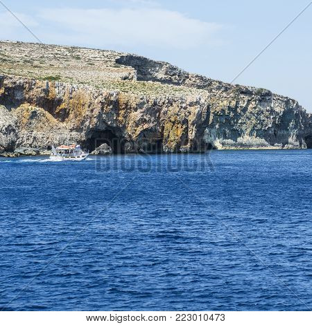 Comino is a small island of the Maltese archipelago between the islands of Malta and Gozo in the Mediterranean Sea. Pleasure craft at the  rugged coastline delineated by sheer limestone cliffs, and dotted with deep caves