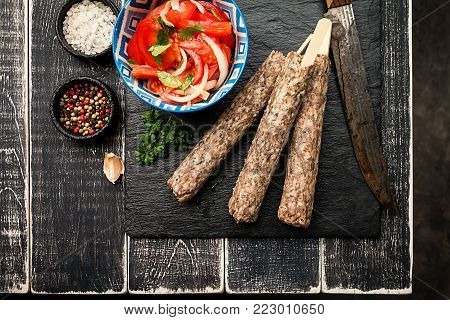 Traditional homemade raw Turkish Adana Urfa Kebab, minced meat kebab, on a plate with tomato salad and zucchini over wooden background, top view
