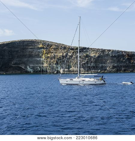 Comino is a small island of the Maltese archipelago between the islands of Malta and Gozo in the Mediterranean Sea. Yacht at the  rugged coastline delineated by sheer limestone cliffs, and dotted with deep caves