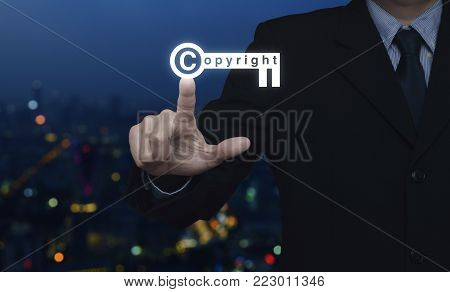 Businessman pressing copyright key icon over blur colorful night light city tower, Copyright and patents concept