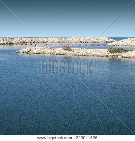 Breakwater protecting the beach of Mediterranean sea in Israel. Red buoys floating in port of Tel Aviv for mooring of yachts.