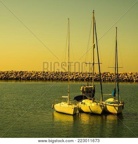 Breakwater protecting the beach of Mediterranean sea in Israel. Port of Tel Aviv for mooring of yachts at sunrise