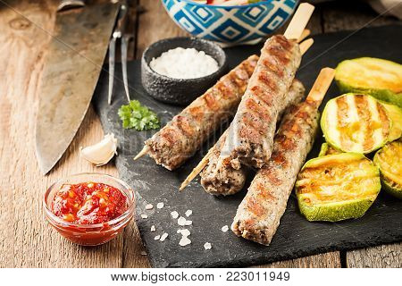 Traditional homemade grilled Turkish Adana Urfa Kebab, minced meat kebab, on slate plate with tomato salad and sauce over wooden background